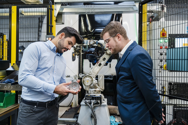 Male colleagues examining machine part in industry