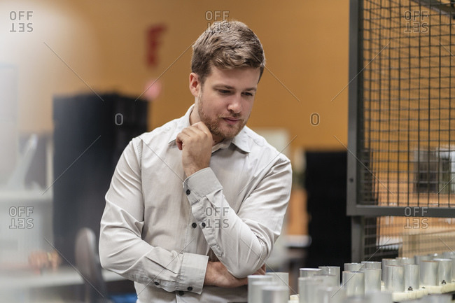 Male entrepreneur examining on product while standing in factory