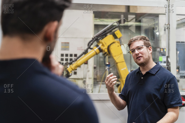 Male coworkers discussing while standing in manufacturing industry