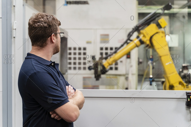 Male factory worker with arms crossed looking at robotic arm through window while standing in factory
