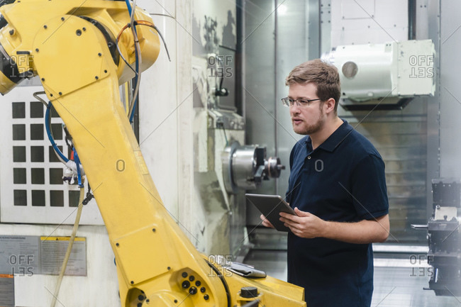 Male manual worker examining robotic arm while holding digital tablet in factory