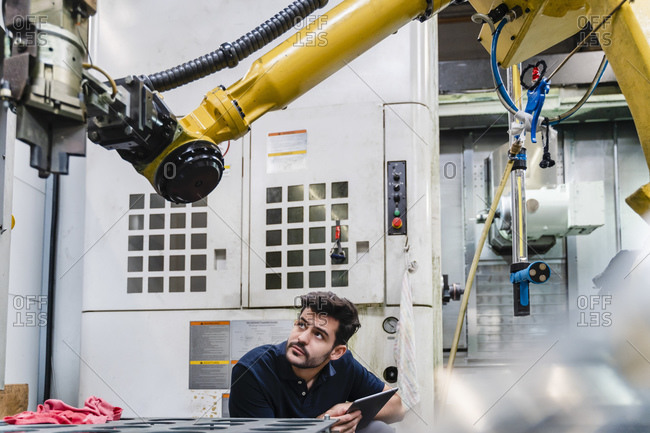 Young male manual worker with digital tablet examining robotic arm in factory