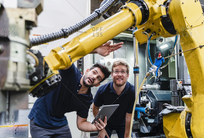 Male coworkers examining robotic arm in manufacturing industry