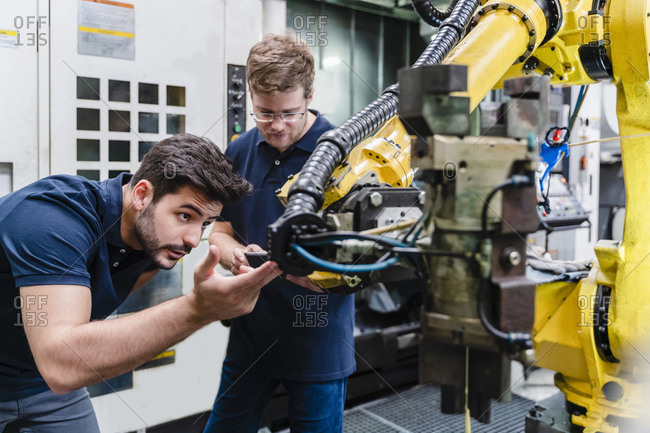 Male coworkers examining robotic arm while standing in manufacturing factory