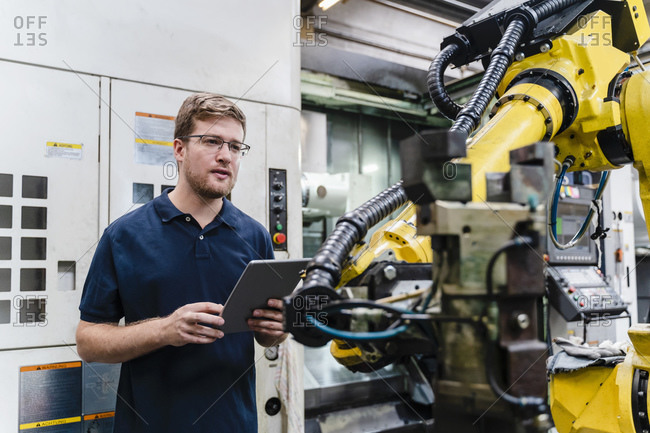 Male worker holding digital tablet while examining in industry