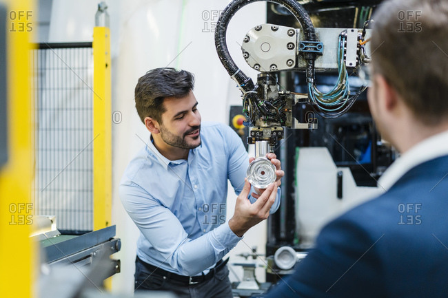 Male entrepreneur explaining about machine part to manager at industry
