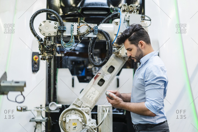 Male entrepreneur examining machine part while standing by robotic arm in industry