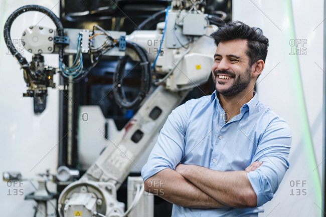 Smiling male entrepreneur with arms crossed looking away while standing by robotic arm at industry