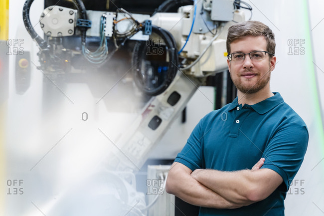 Confident male worker with arm crossed standing against industrial robot at factory