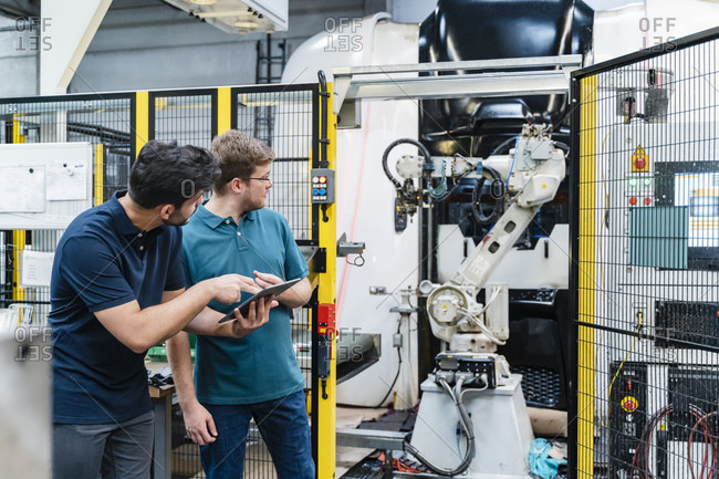 Male coworkers holding digital tablet looking at robotic arm while standing in manufacturing industry