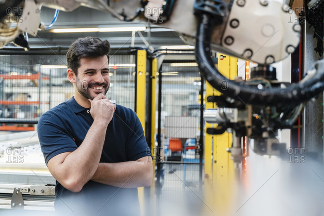 Smiling male worker with hand on chin looking at robotic arm in manufacturing industry