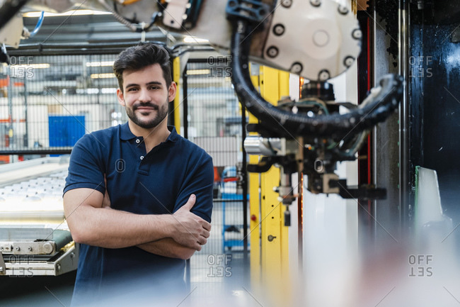 Smiling male worker with arms crossed standing at industry