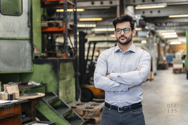Confident businessman with arms crossed standing at manufacturing industry