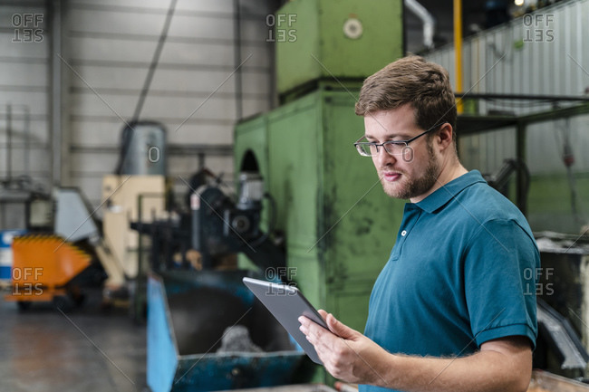 Male factory worker using digital tablet while standing in manufacturing industry
