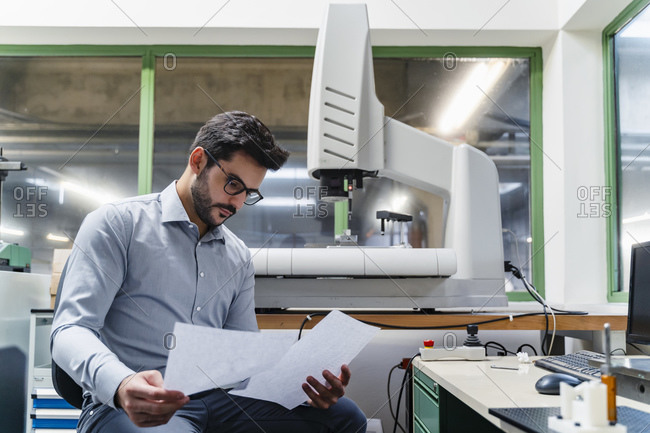 Male entrepreneur reading document while sitting in industry