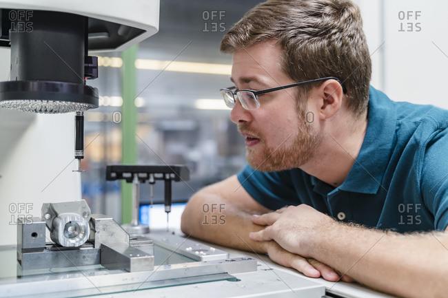 Male factory worker analyzing surveyor machine in factory