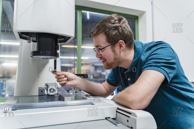 Smiling male factory worker analyzing surveyor machine at industry