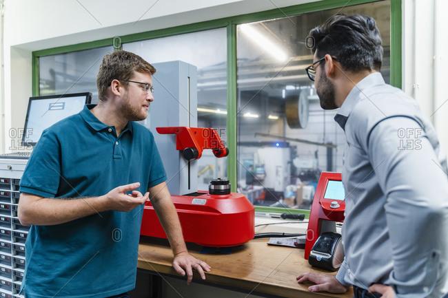Male worker explaining surveyor machine to businessman at industry