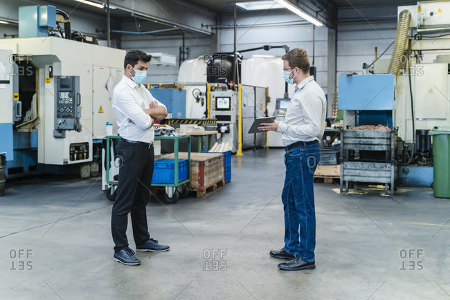 Male coworkers discussing while maintaining social distancing in factory