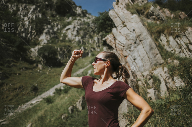 Smiling woman flexing muscles while standing against rock formation on sunny day