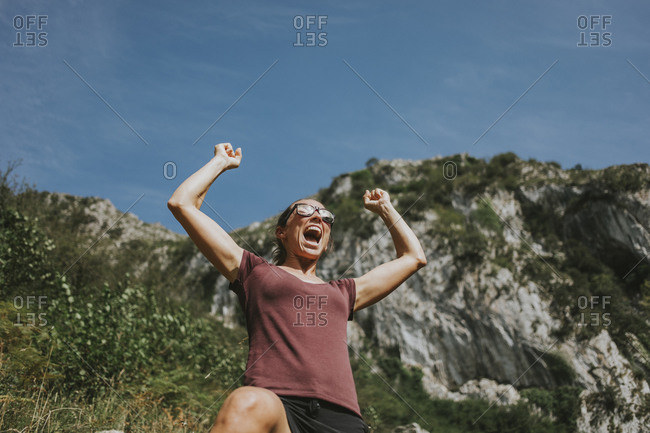 Smiling female trekker celebrating victory with arms raised shouting against sky on sunny day