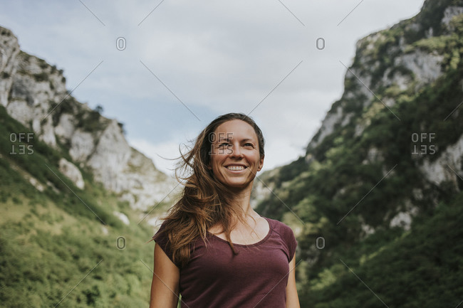 Smiling female trekker with long brown hair looking away while standing against mountain range