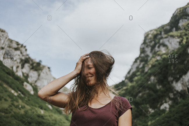 Happy female trekker with tousled long brown hair against mountain range