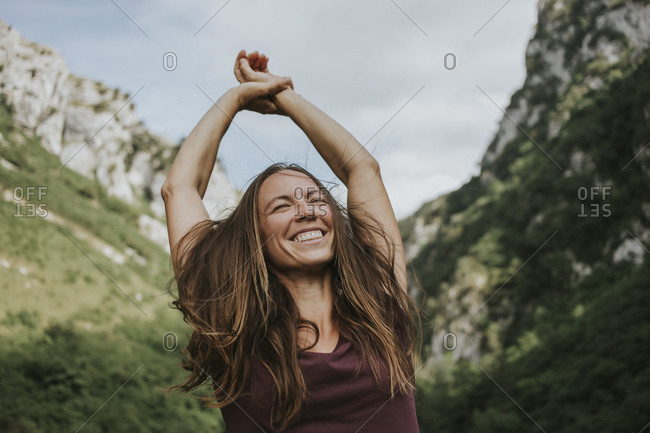 Cheerful female trekker with tousled brown hair enjoying during hiking