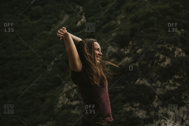 Happy female trekker enjoying while stretching during hiking