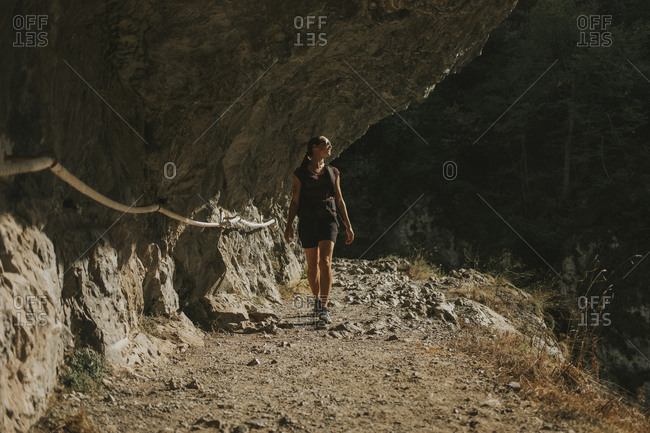 Woman looking away while walking by rock formation