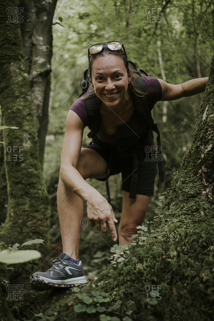 Smiling female trekker bending over by plants in forest