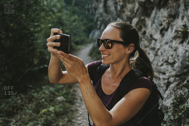 Smiling woman photographing while hiking