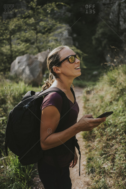Woman looking away while holding smart phone for navigation during hiking on sunny day