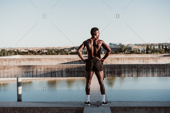 Male athlete with hand on hip standing against sky during sunny day