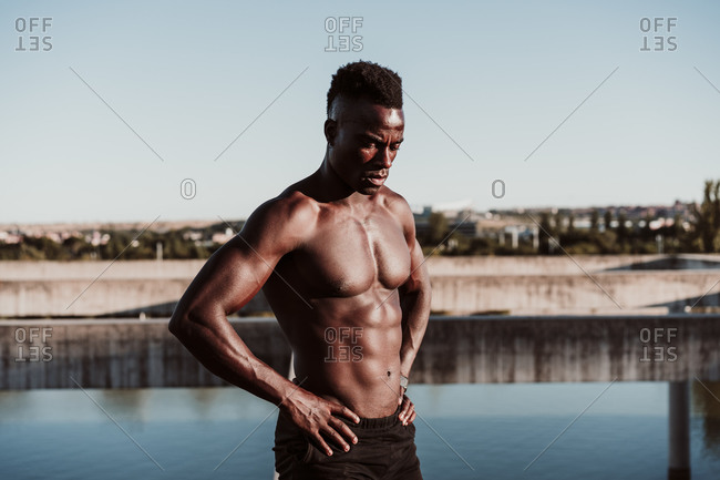 Young sportsman looking down with hand on hip standing against clear sky