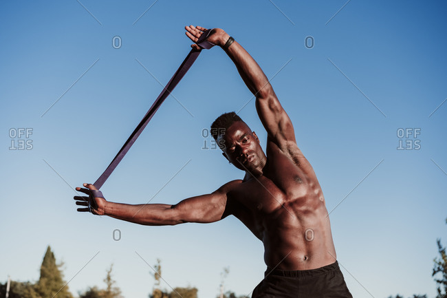 Male athlete doing resistance band exercise while standing against clear blue sky