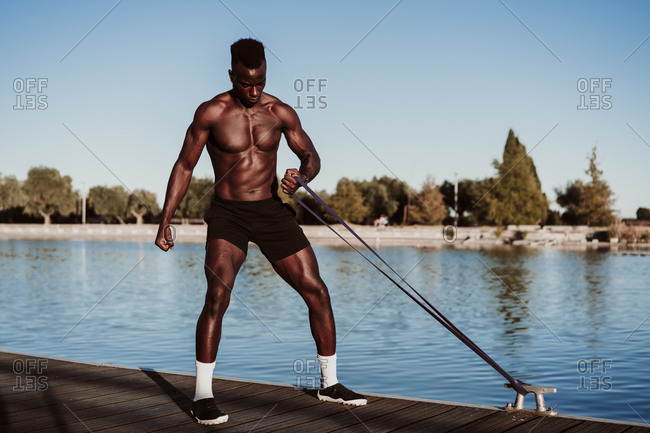Sportsman pulling resistance band while standing on pier against sea during sunset