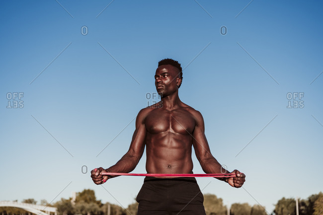 Male athlete looking away while stretching resistance band standing against clear sky during sunset