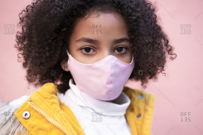 Girl wearing pink face mask standing against pink wall