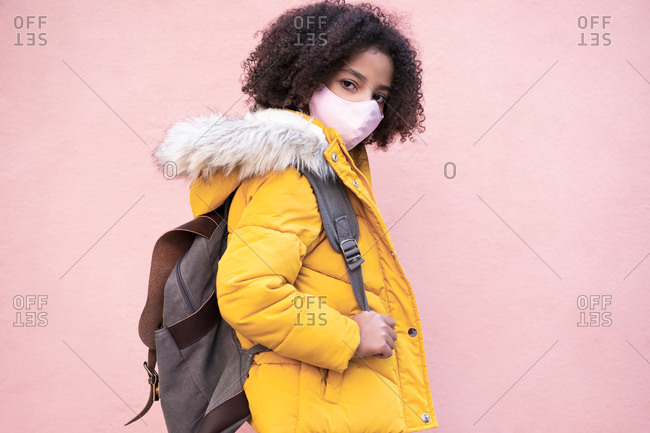Girl with face mask carrying backpack while standing against pink wall