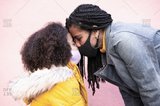 Mother and daughter wearing face mask standing face to face against pink wall