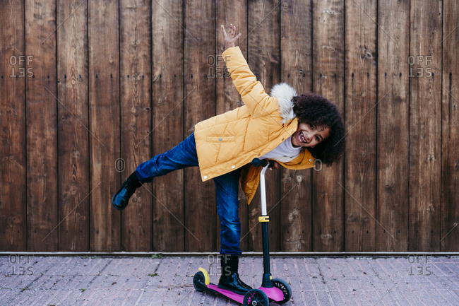 Playful girl riding push scooter against wooden wall