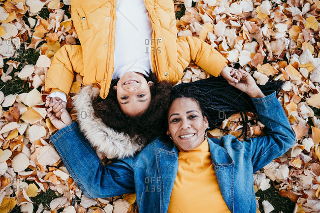 Smiling mother and daughter lying on fallen leaves at park