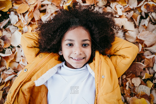 Smiling girl with hands behind head lying on fallen leaf at park