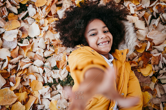 Smiling girl stretching hand while lying on fallen leaf at park