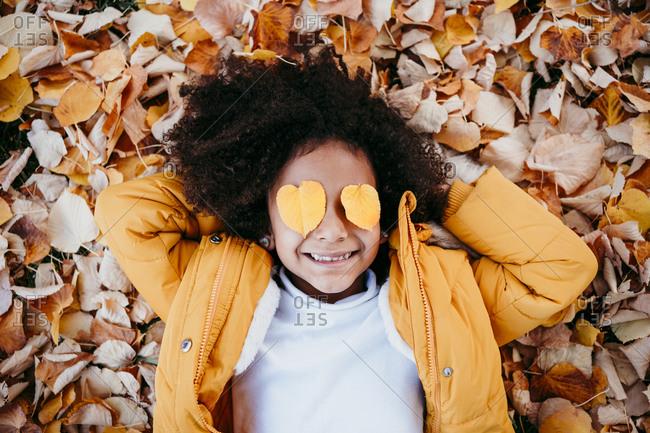 Smiling girl with heart shape leaf on eyes lying on fallen leaf at park