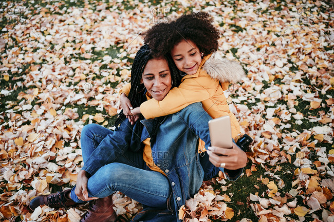 Girl embracing mother taking selfie through smart phone while sitting on autumn leaves