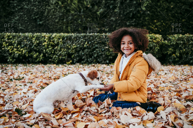 Smiling girl playing with puppy while sitting at park