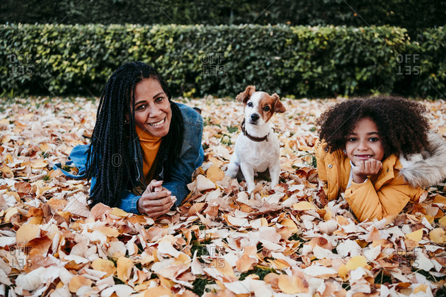 Smiling woman and daughter lying on dry leaf by dog sitting at park
