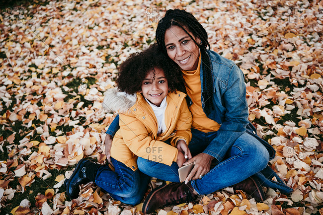 Mother and daughter smiling while sitting on fallen leaves at park